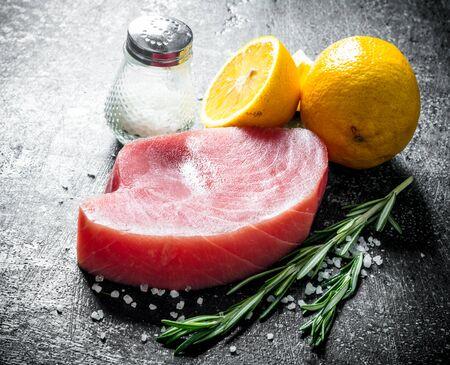 Fresh uncooked tuna steak with lemon, salt and rosemary. On dark rustic background Stock Photo