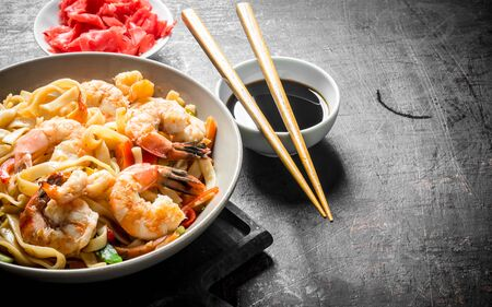 Noodles in a plate with shrimp and vegetables on the cutting Board. On dark rustic background Stockfoto