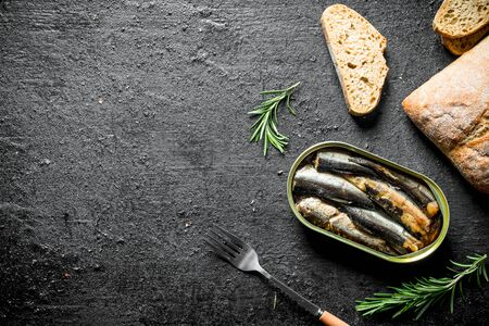 Sprats with slices of bread and rosemary. On black rustic background