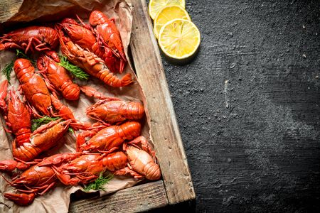 Boiled crayfish on a wooden tray with slices of lemon. On black rustic background