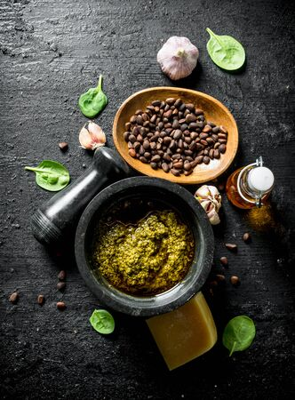 Pesto sauce with olive oil, pine nuts and Parmesan. On black rustic background Фото со стока