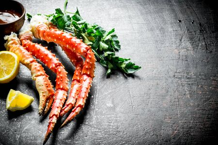 Boiled crab with herbs, sauce and sliced lemon. On dark rustic background Stok Fotoğraf - 124763507