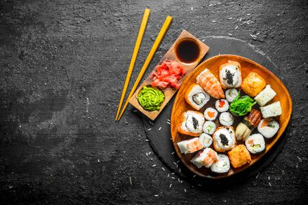 Japanese maki, rolls and sushi with ginger, soy sauce and wasabi. On black rustic background