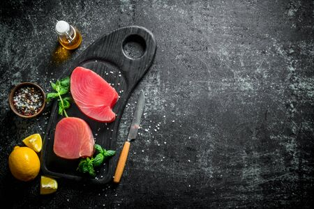 Raw tuna fillet on a cutting Board with mint, lemon and spices. On dark rustic background Stock Photo
