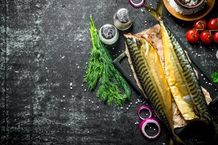 Smoked mackerel with spices and dill. On dark rustic background