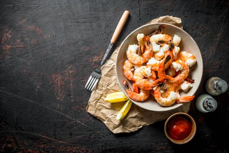 Freshly cooked shrimps with spices, sauce and lemon. On dark rustic background Stok Fotoğraf - 124763560