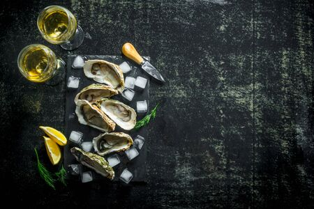 Appetizing raw oysters on a stone Board with ice cubes and glasses of white wine. On dark rustic background