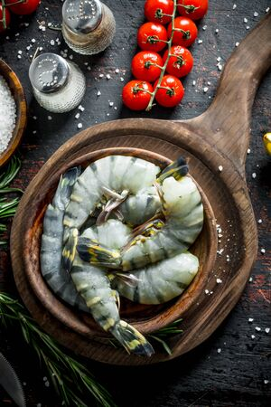 Raw shrimps with spices, tomatoes on a branch and rosemary. On dark rustic background Stock Photo