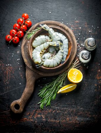 Raw shrimps in a plate on a cutting Board with cherry tomatoes, rosemary and cut lemon. On dark rustic background