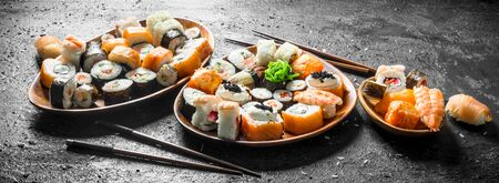 Different kinds of Japanese sushi rolls with salmon, shrimp and vegetables. On black rustic background Banque d'images - 124763568