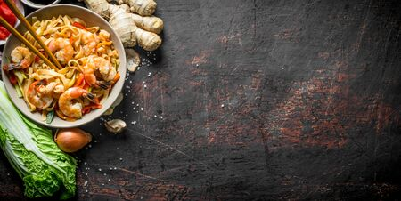 Noodles with shrimps, onions and Chinese cabbage. On dark rustic background Banque d'images - 124763630