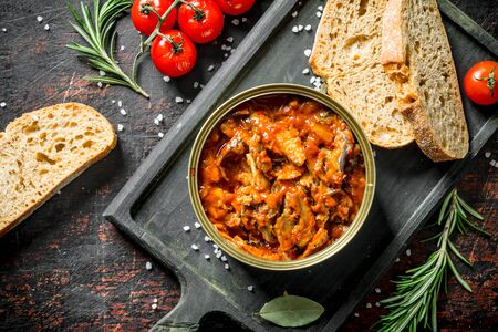 Sprat in tomato sauce with bread, cherry tomatoes and rosemary. On dark rustic background Stok Fotoğraf