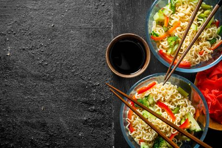 Instant noodles in bowls with vegetables, ginger and soy sauce. On black rustic background