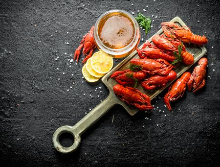 Boiled crayfish on a cutting Board with beer and lemon slices. On black rustic background Stok Fotoğraf - 124763636