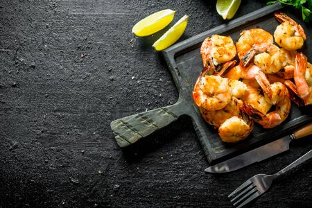 Delicious shrimps on the cutting Board. On black rustic background Stok Fotoğraf - 124763642