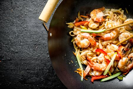 Fragrant Asian Udon noodles in a wok pan. On black rustic background Banque d'images - 124763646