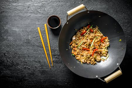 Fragrant wok rice with chicken and vegetables. On dark rustic background