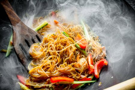 Hot Asian cellophane noodles with vegetables and salmon. On rustic background Stok Fotoğraf