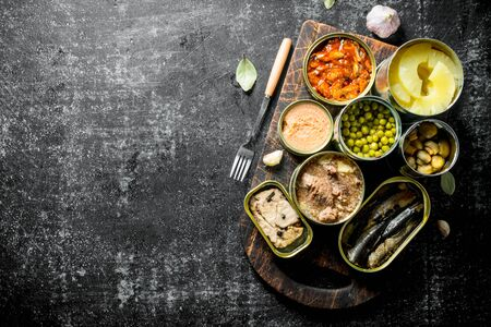 Open tin cans with various canned food on wooden cutting Board. On dark rustic background Banque d'images - 124763676