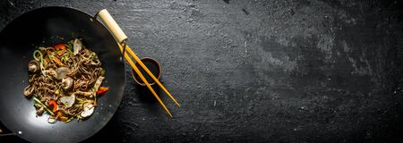 Fragrant soba noodles in a wok pan. On black rustic background Stok Fotoğraf