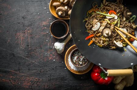 Fragrant Asian soba with spices, beef, vegetables and mushrooms. On dark rustic background