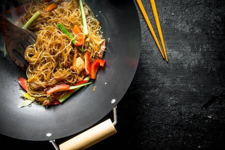 Fragrant Chinese cellophane noodles in a frying pan wok with salmon and vegetables. On dark rustic background