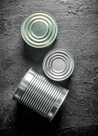 Closed metal cans of canned food. On black rustic background Stok Fotoğraf