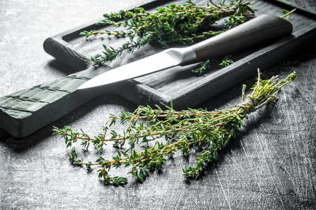 Thyme with a cutting Board and a knife. On dark rustic background