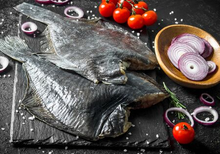 Raw fish flounder with chopped onions, tomatoes and rosemary. On black rustic background Imagens - 124763778