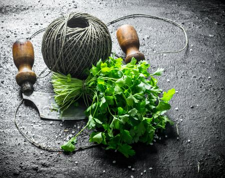 Fresh parsley with old twine and a knife. On black rustic background Stok Fotoğraf