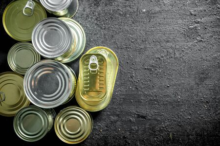 Set of different kinds of tin cans with canned food. On black rustic background Banque d'images - 124763783