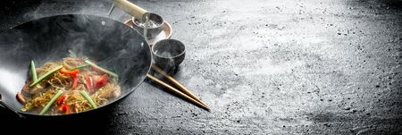 Chinese wok. Hot Asian cellophane noodles in a frying pan wok. On dark rustic background Stok Fotoğraf