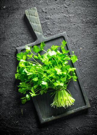 Fresh parsley on the cutting Board. On black rustic background