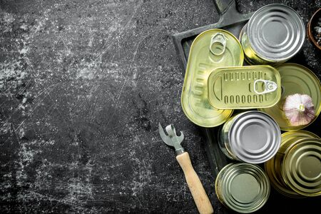 Set of different kinds of tin cans with canned food on a cutting Board with garlic and a opener. On dark rustic background 스톡 콘텐츠