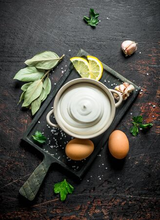 Mayonnaise with Bay leaf, eggs and garlic. On dark rustic background