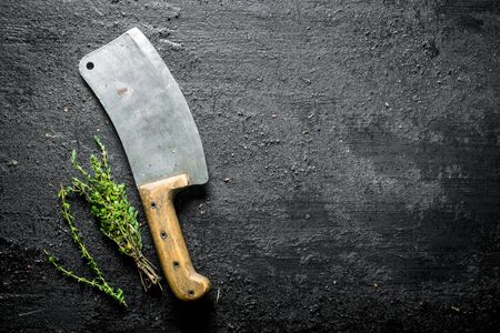 Thyme with a big knife. On black rustic background
