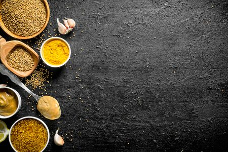 Different types of mustard with garlic cloves. On black rustic background Stok Fotoğraf