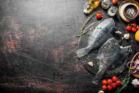 Raw fish flounder with spices, tomatoes, chopped onion and garlic. On dark rustic background