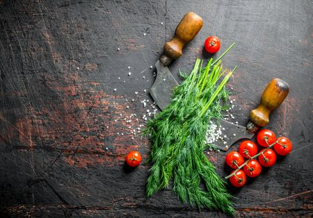 Bunch of fresh dill with tomatoes. On dark rustic background