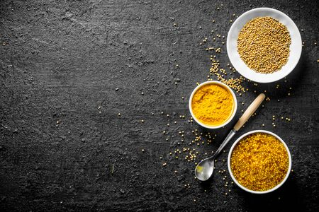 Different types of mustard. On black rustic background