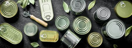 Set of different kinds of tin cans with canned food. On black rustic background Stok Fotoğraf