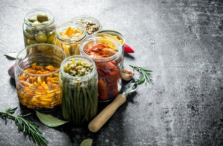 Pickled food in jars of rosemary and garlic. On dark rustic background