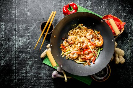 Chinese wok pasta with shrimp and fresh vegetables. On dark rustic background