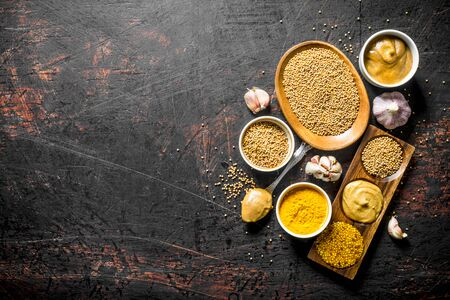 Assortment of different types of mustard with garlic. On dark rustic background Stok Fotoğraf