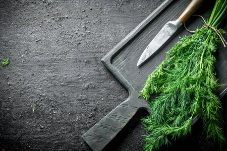 Fresh dill on a cutting Board with a knife. On black rustic background Banque d'images - 124763727