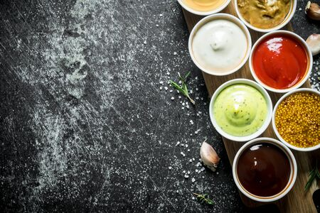 Different sauces in the bowls on the cutting Board. On dark rustic background Banque d'images - 124763732