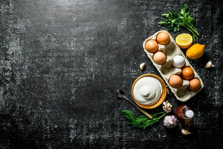 Mayonnaise with eggs, herbs and garlic. On dark rustic background