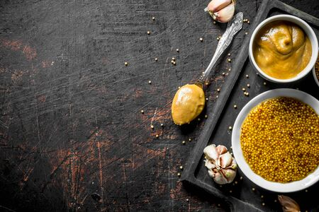 Different kinds of mustard on the cutting Board. On dark rustic background