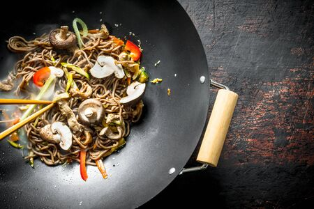 Hot Asian soba noodles with vegetables, mushrooms and sauce. On rustic background Stok Fotoğraf