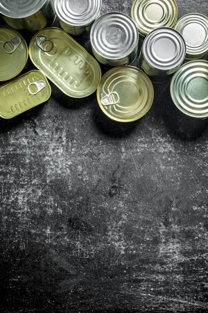 A group of closed aluminum cans with canned food. On dark rustic background